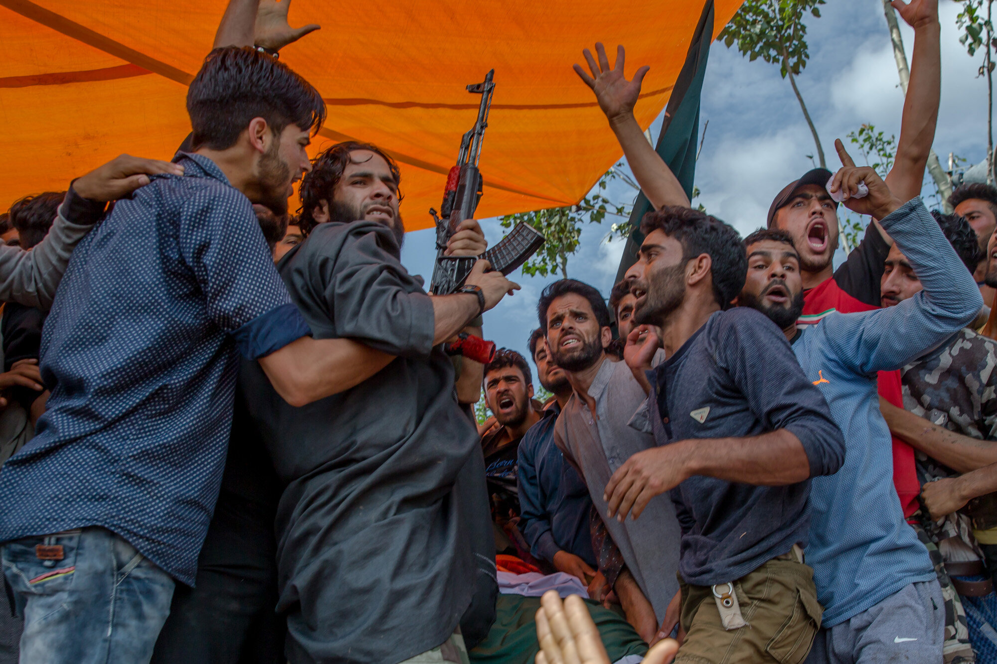 A Kashmiri militant fires his gun to salute fallen comrade Suhail Ahmed,who was killed in an ambush by Indian government forces in Tantraypora, some 85 kilometers (53 miles) south of Srinagar, Indian controlled Kashmir, Thursday, Aug. 3,2017. (AP Photo/Dar Yasin)