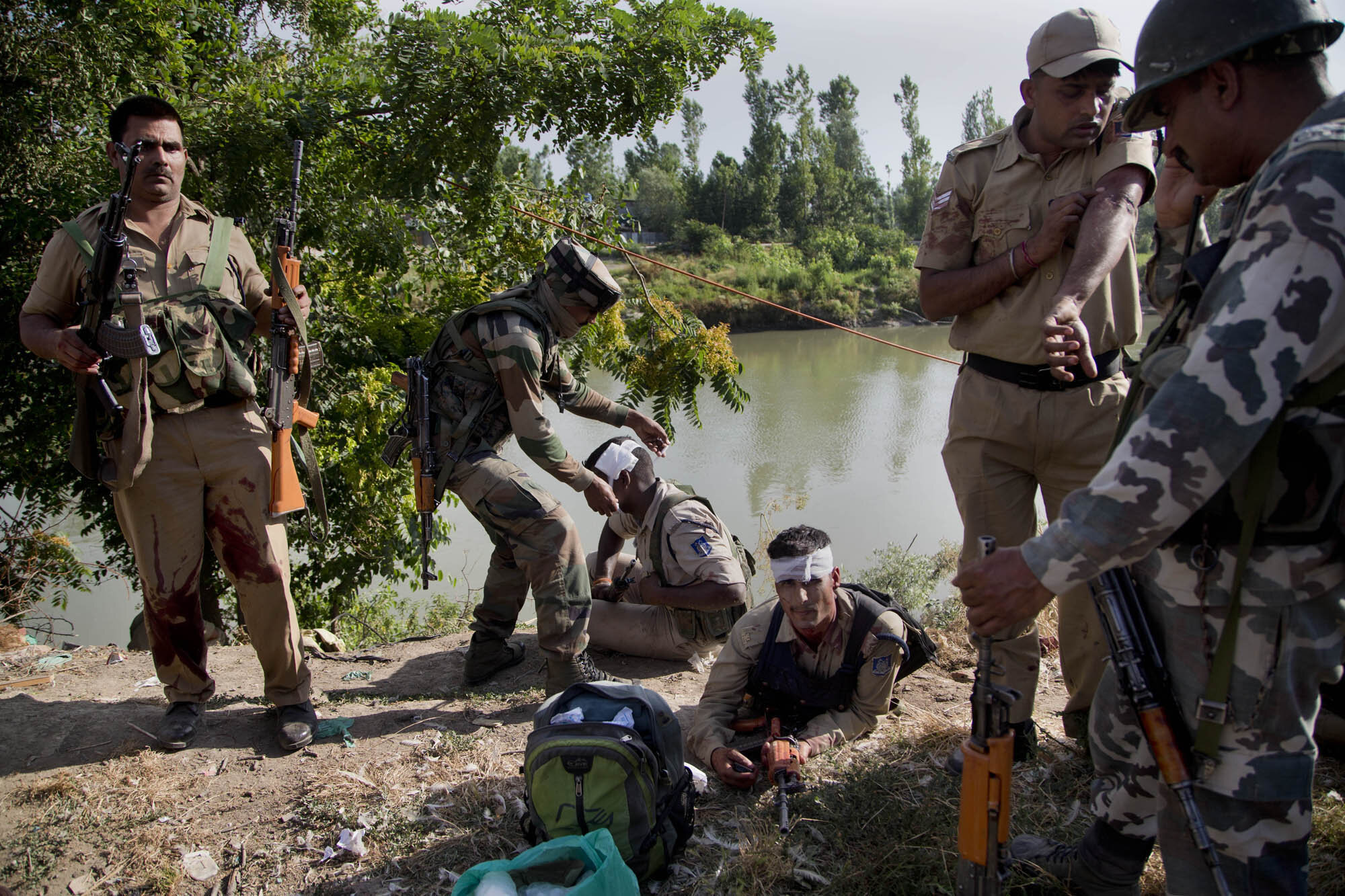 An Indian army soldier, second left, gives first aid to paramilitary soldiers who were injured in a highway ambush in Pampore, on the outskirts of Srinagar, Indian controlled Kashmir, June 25, 2016. (AP Photo/Dar Yasin)
