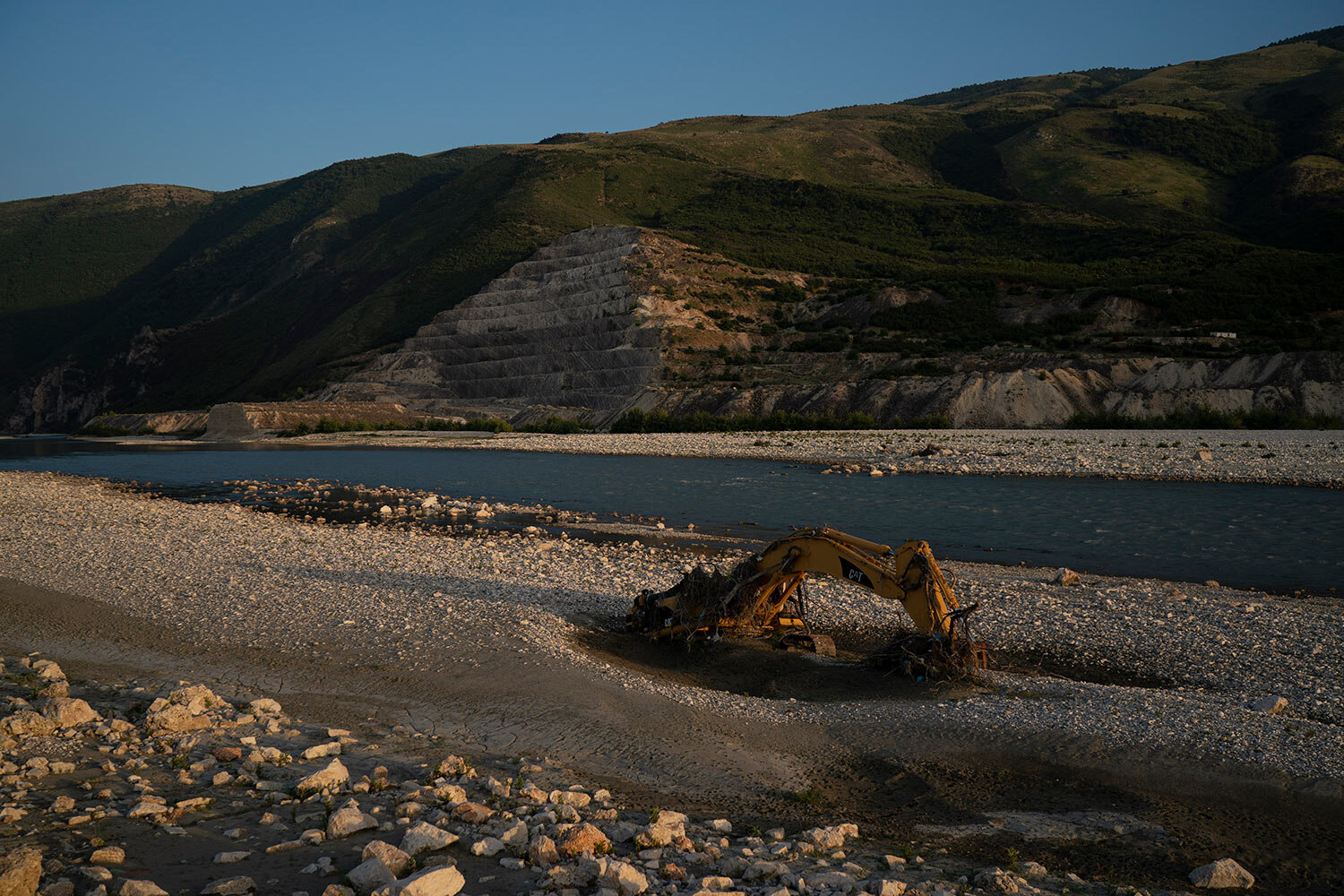 An abandoned bulldozer sits on the banks of the Vjosa River at the construction site of the Kalivac dam in Albania. (AP Photo/Felipe Dana)