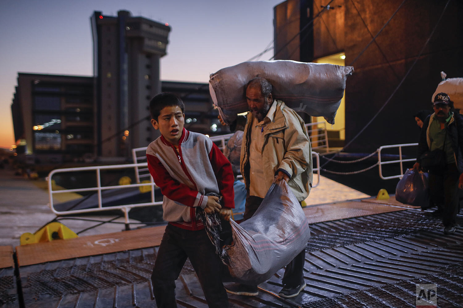 Migrants and refugees carry their belongings as they disembark from a ferry at the port of Piraeus, near Athens, Tuesday, Oct. 1, 2019. (AP Photo/Petros Giannakouris)