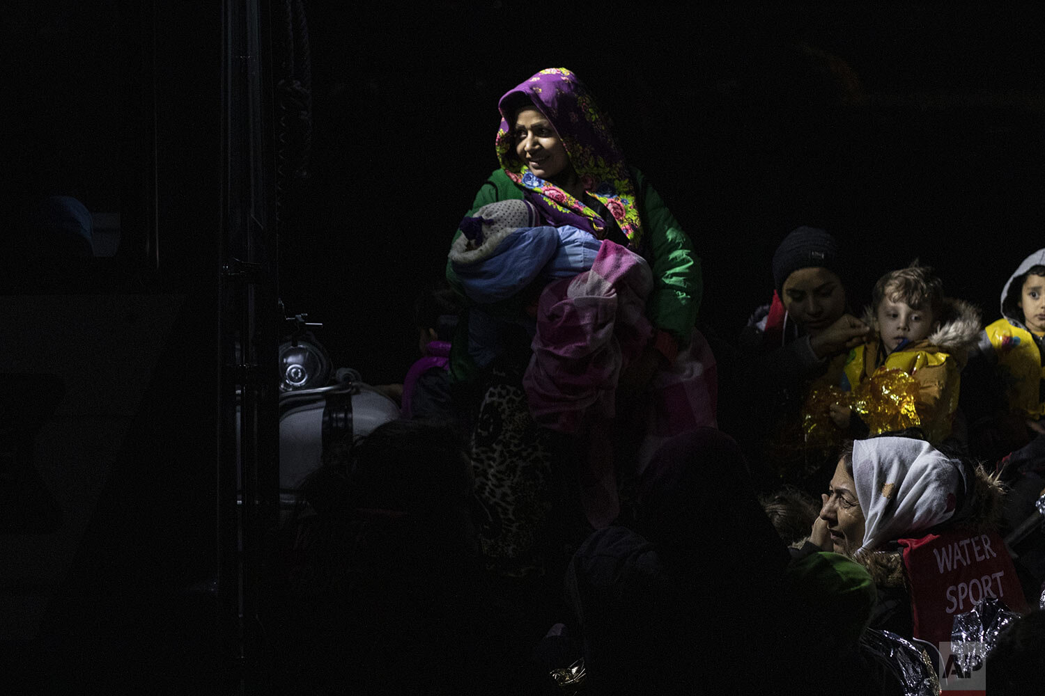 An Afghan woman holds her baby following a rescue operation by a Frontex patrol vessel as she arrives with other migrants at the harbor of Skala Sikamias, on the Greek island of Lesbos, early Sunday Oct. 6, 2019. (AP Photo/Petros Giannakouris)