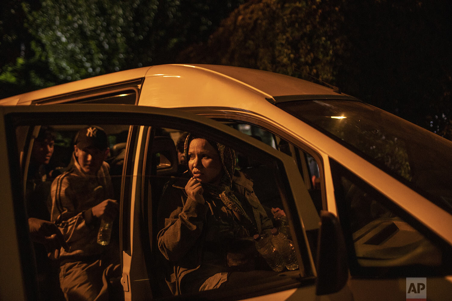 Newly-arrived migrants and refugees look out from a van at the harbor of Skala Sikamias, on the Greek island of Lesbos, early Thursday, Oct. 3, 2019. (AP Photo/Petros Giannakouris)