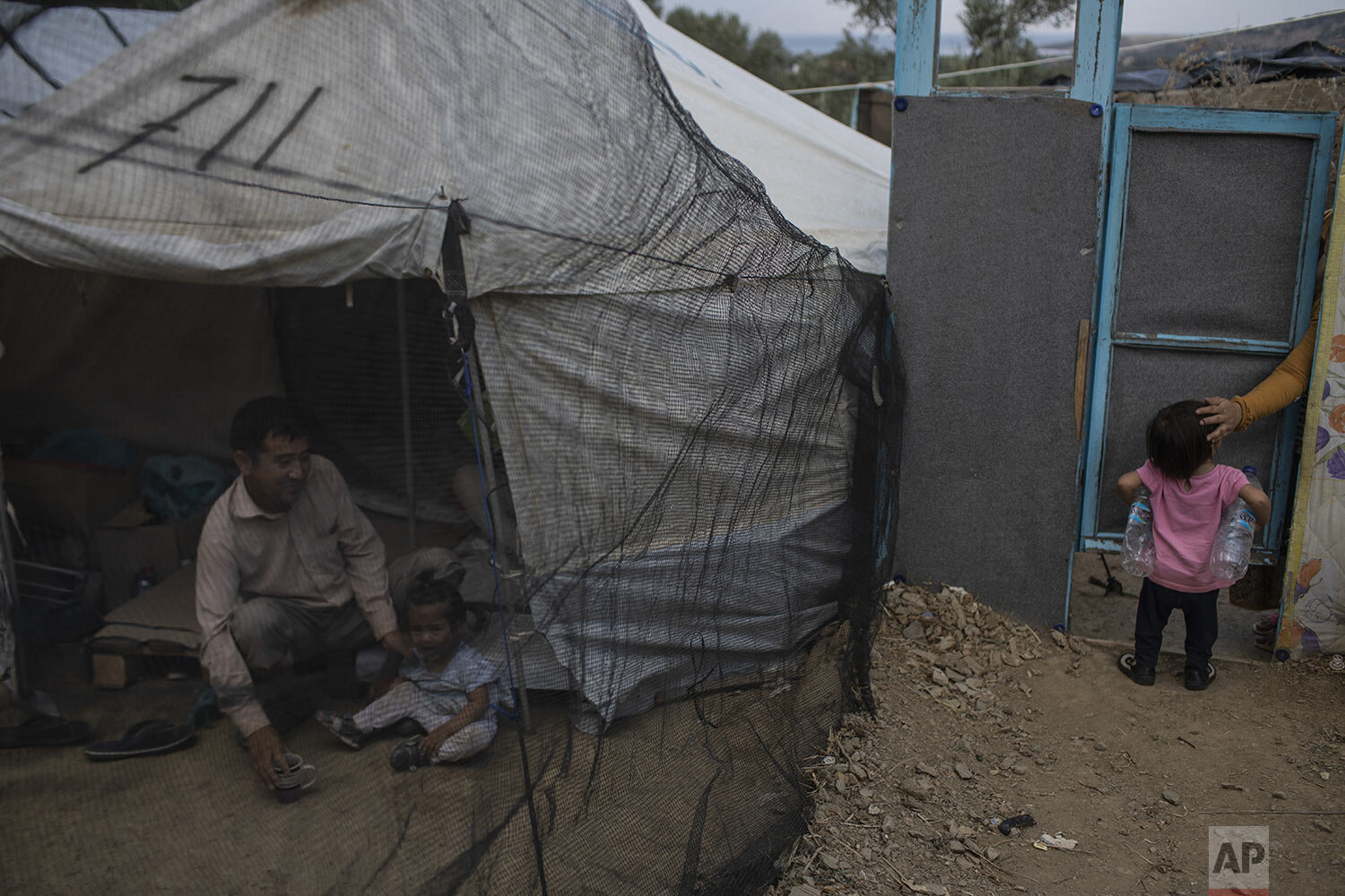 Abdul Hanoi, 38, from Afghanistan, sits next to his daughter Yesna outside their tent in a makeshift refugee and migrant camp on the fringes of the overcrowded Moria camp on the Greek island of Lesbos, Friday Oct. 4, 2019. (AP Photo/Petros Giannakouris)