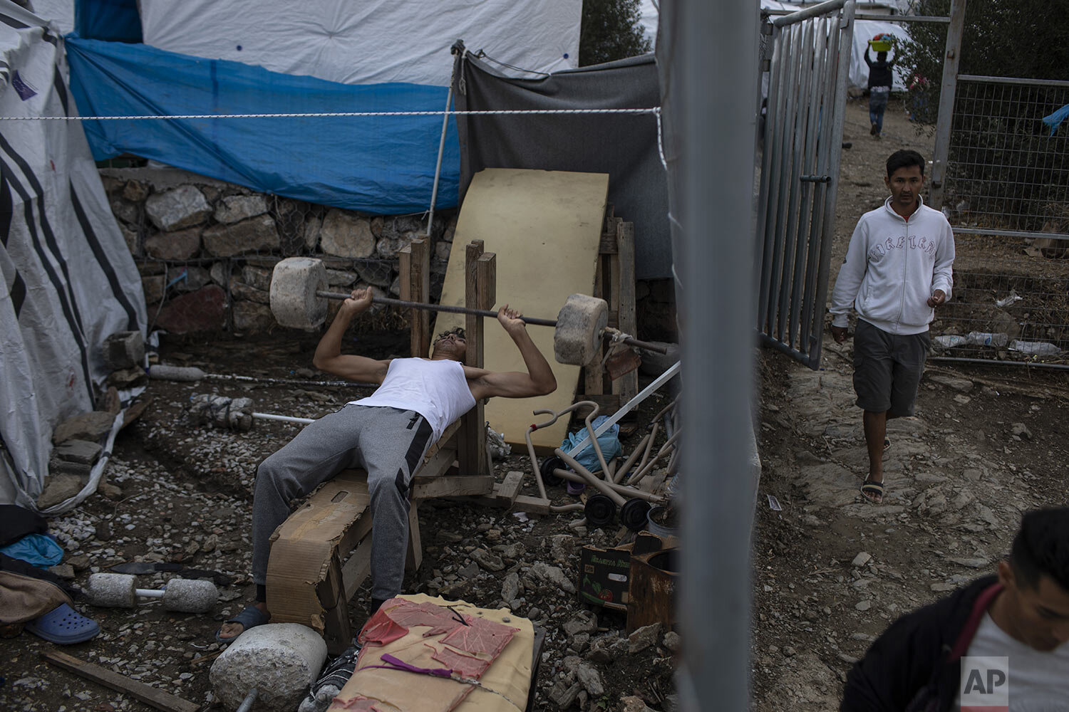 A man from Kabul, Afghanistan, works out on a makeshift bench in the overcrowded Moria refugee and migrant camp, Lesbos island, Greece, Tuesday, Oct. 8, 2019. (AP Photo/Petros Giannakouris)