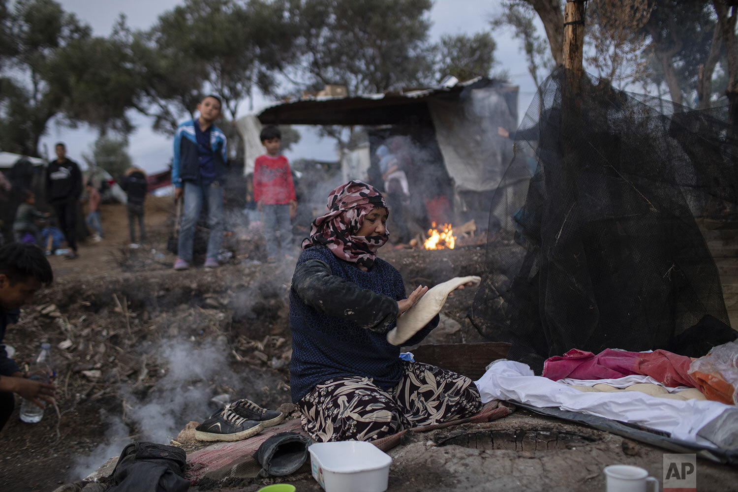 Pargoul Rahmani, 57, makes bread at a makeshift bakery in the overcrowded Moria refugee and migrant camp, Lesbos island, Greece, Tuesday, Oct. 8, 2019. (AP Photo/Petros Giannakouris)