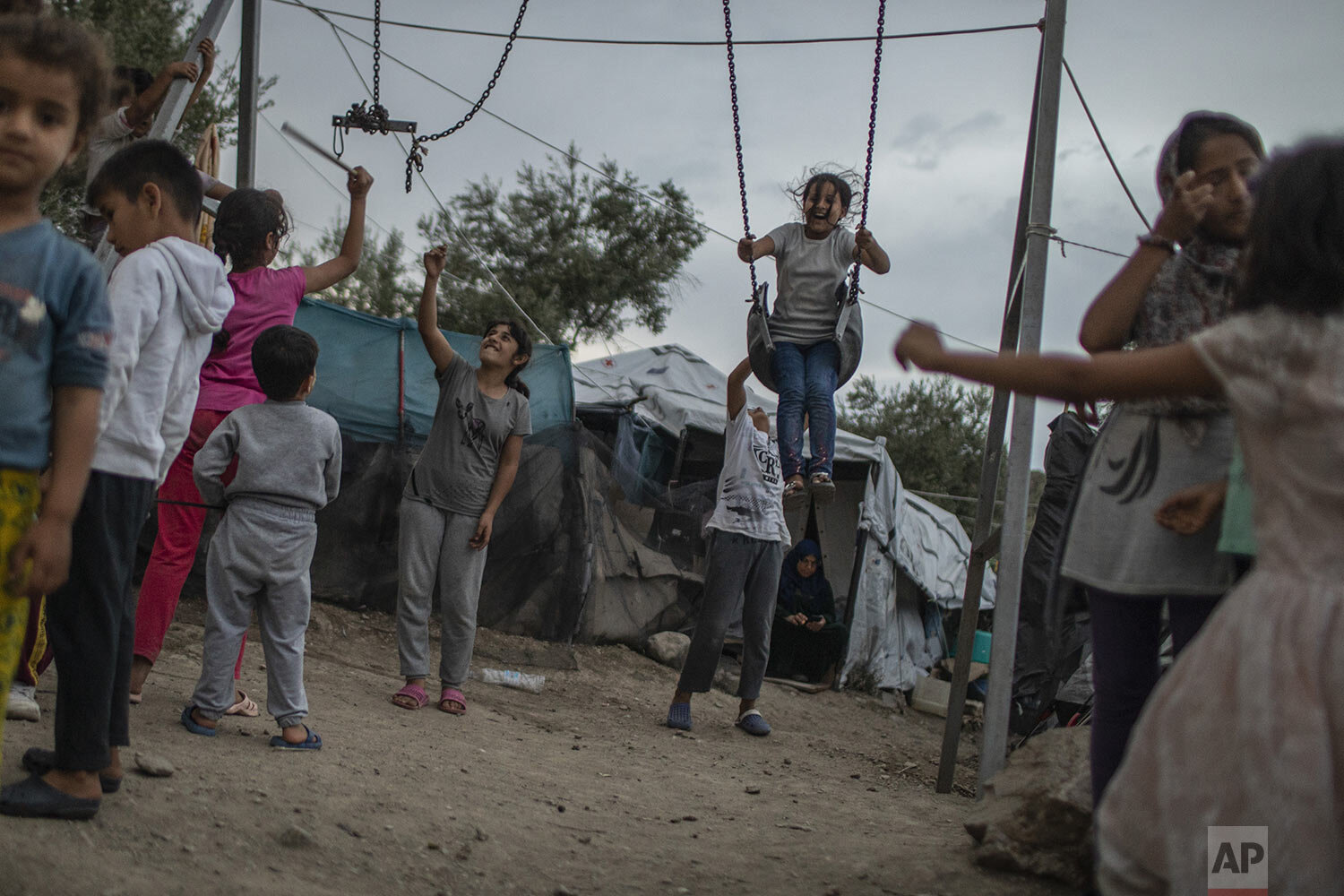 Children play near swings at the Moria refugee and migrant camp on the Greek island of Lesbos, Friday Oct. 4, 2019. (AP Photo/Petros Giannakouris)