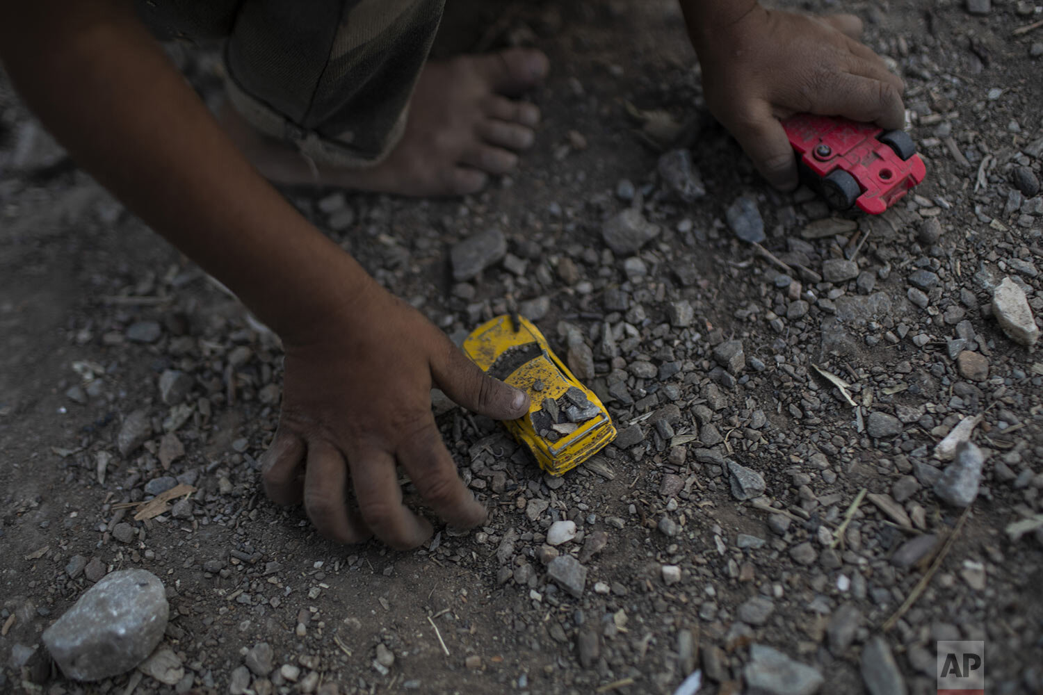 A Syrian boy plays with a toy car at the Moria refugee and migrant camp on the Greek island of Lesbos, Thursday, Oct. 3, 2019. (AP Photo/Petros Giannakouris)