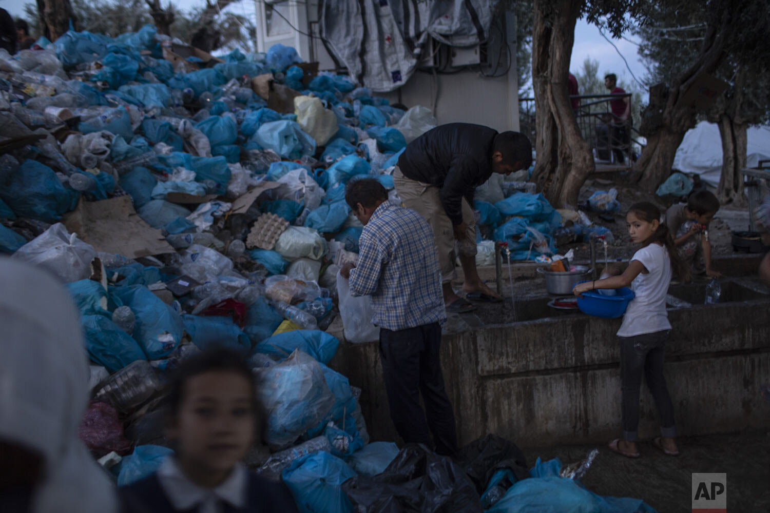 People use the public wash area, in front of a pile of garbage bags at a makeshift refugee and migrant camp next to the overcrowded Moria camp on the Greek island of Lesbos, Thursday, Oct. 3, 2019.. (AP Photo/Petros Giannakouris)