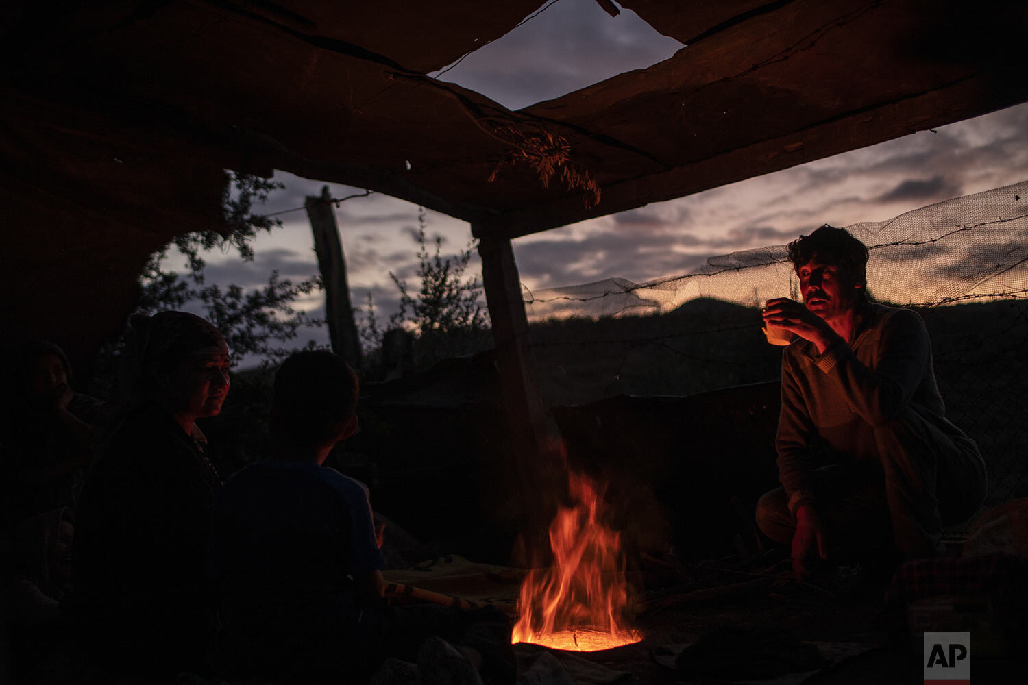 People from Afghanistan drink tea over the fire of a makeshift bakery in the overcrowded Moria refugee and migrant camp, Lesbos island, Greece, Tuesday, Oct. 8, 2019. (AP Photo/Petros Giannakouris)
