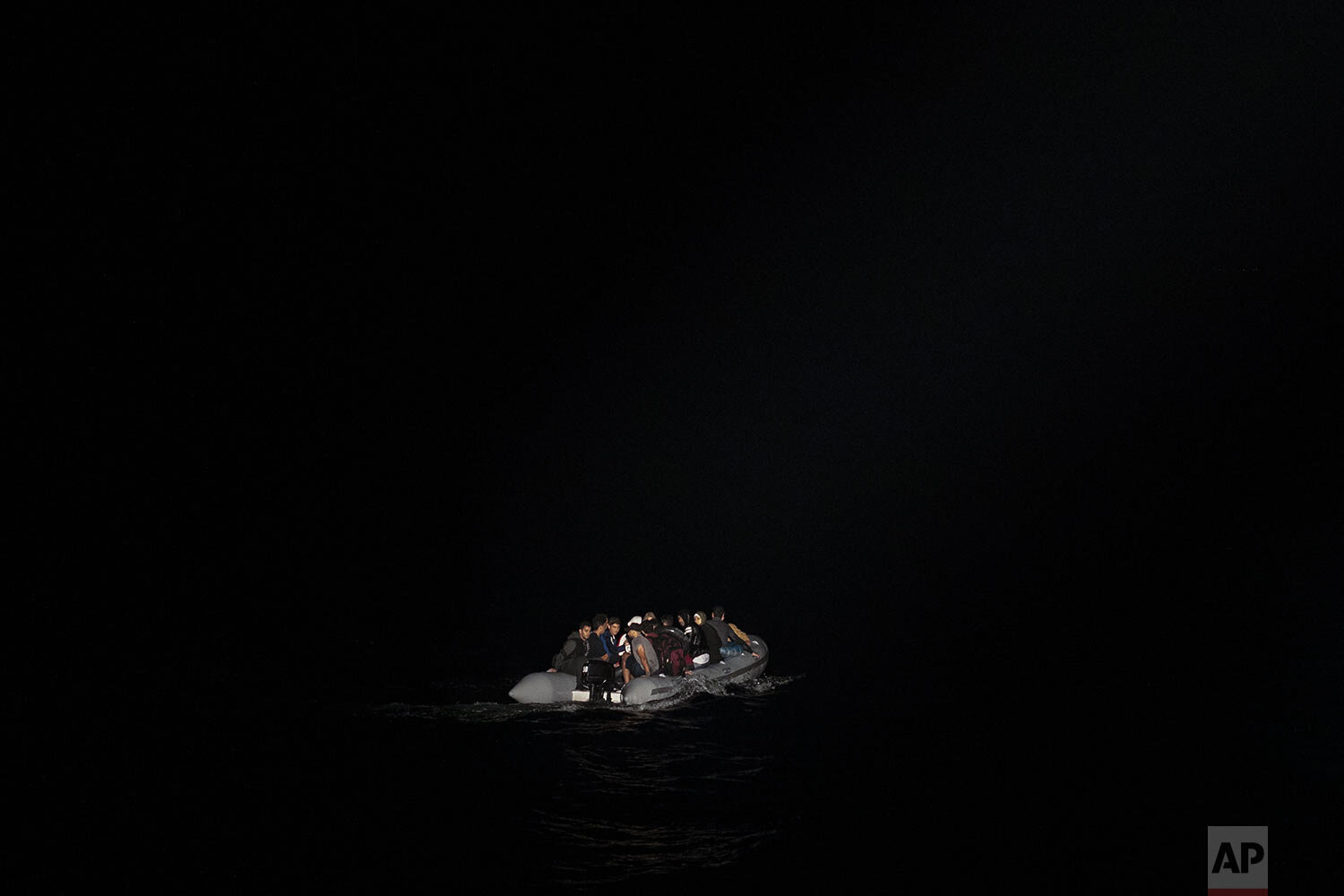 Refugees and migrants in a dinghy are lit by a a Greek coast guard patrol boat's spotlight during a rescue operation near the eastern Aegean Sea island of Samos, early Thursday, Sept. 26, 2019. (AP Photo/Petros Giannakouris)