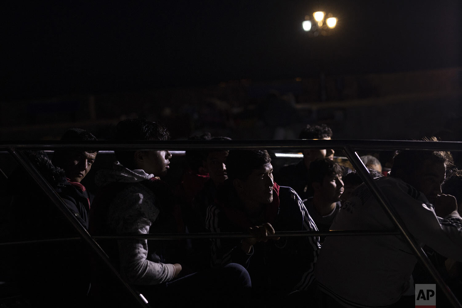 Migrants and refugees sit in a Frontex patrol boat in the tiny harbor of Skala Sikamias, on the Greek island of Lesbos, early Thursday, Oct. 3, 2019. (AP Photo/Petros Giannakouris)