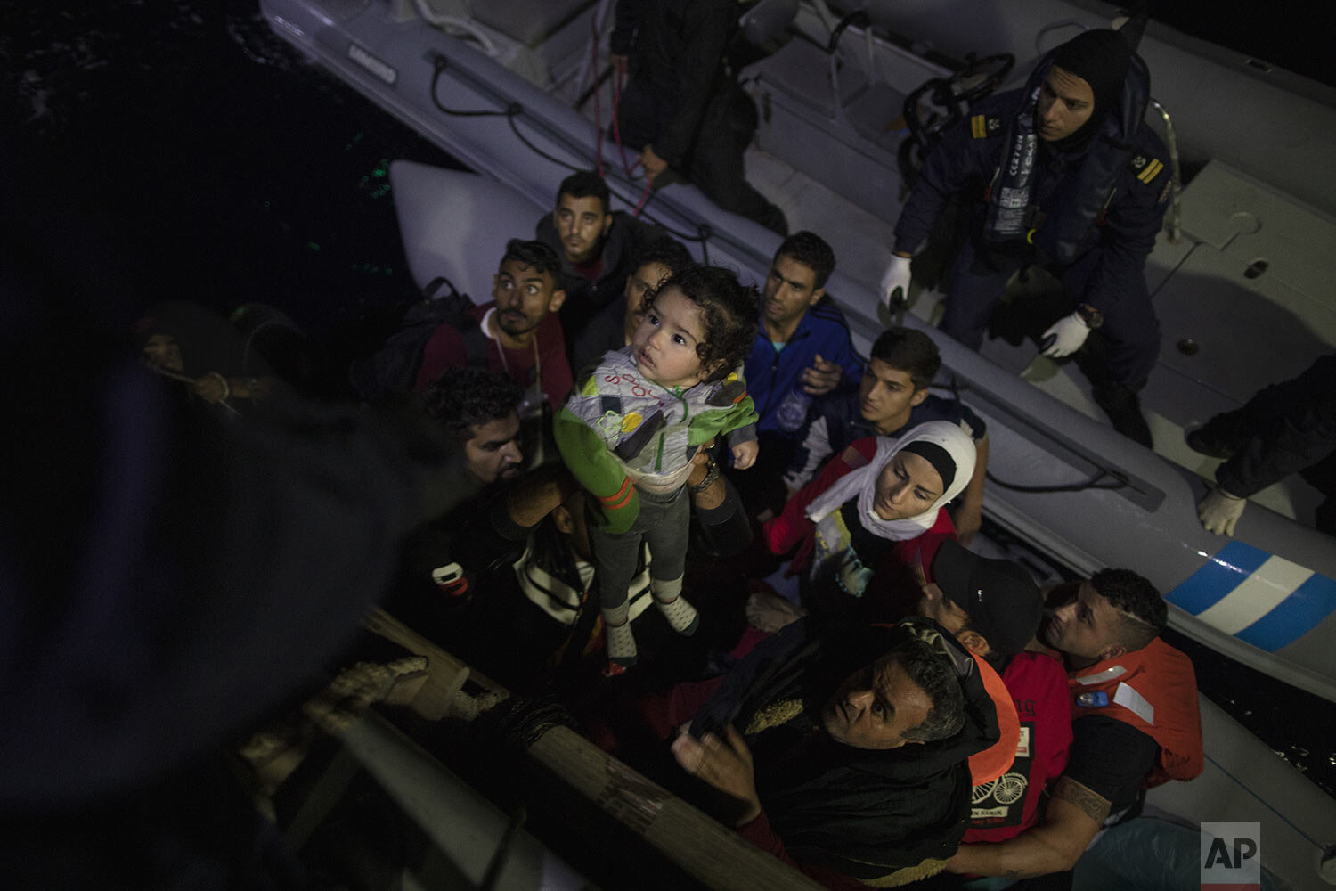 Refugees and migrants are transferred from their dinghy onto a Greek coast guard patrol boat during a rescue operation near the eastern Aegean Sea island of Samos, early Thursday, Sept. 26, 2019. (AP Photo/Petros Giannakouris)