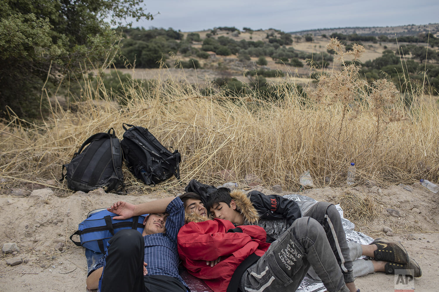 Exhausted Afghan youths sleep on the ground near the town of Madamados after their arrival with other migrants and refugees on a rubber boat from Turkey, at Lesbos Island, Greece, Monday, Oct. 7, 2019. (AP Photo/Petros Giannakouris)