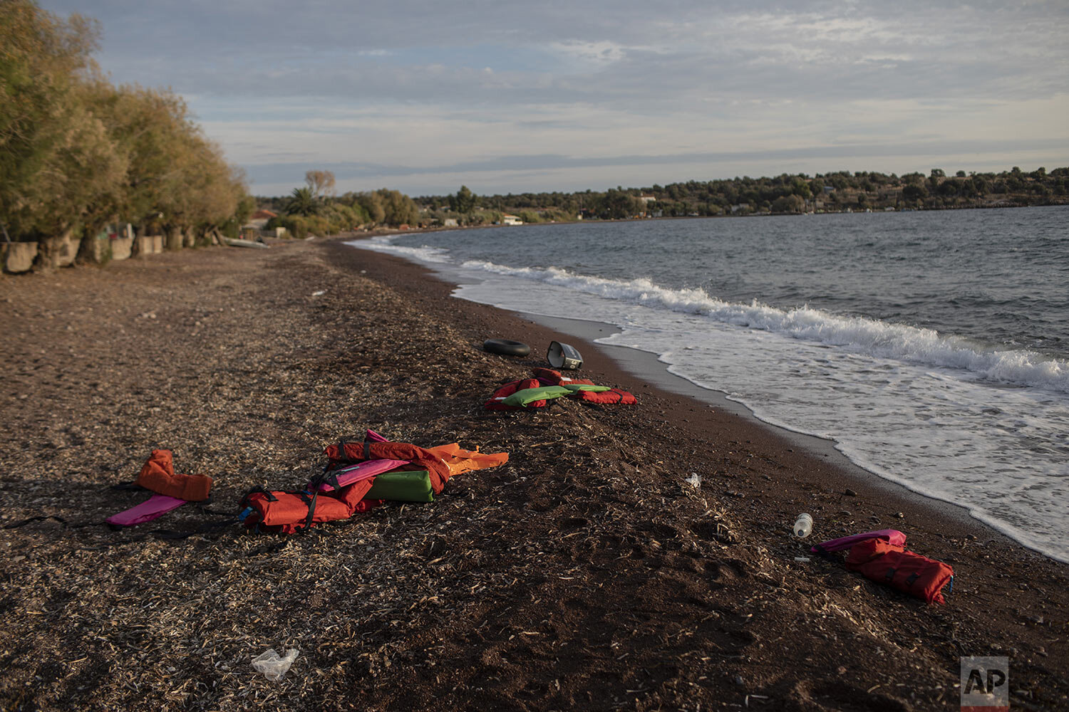 Life vests lay on a beach at the seaside village of Tsonia, Lesbos island, Greece after the arrival of refugees and migrants on a rubber boat from Turkey, Monday, Oct. 7, 2019. (AP Photo/Petros Giannakouris)