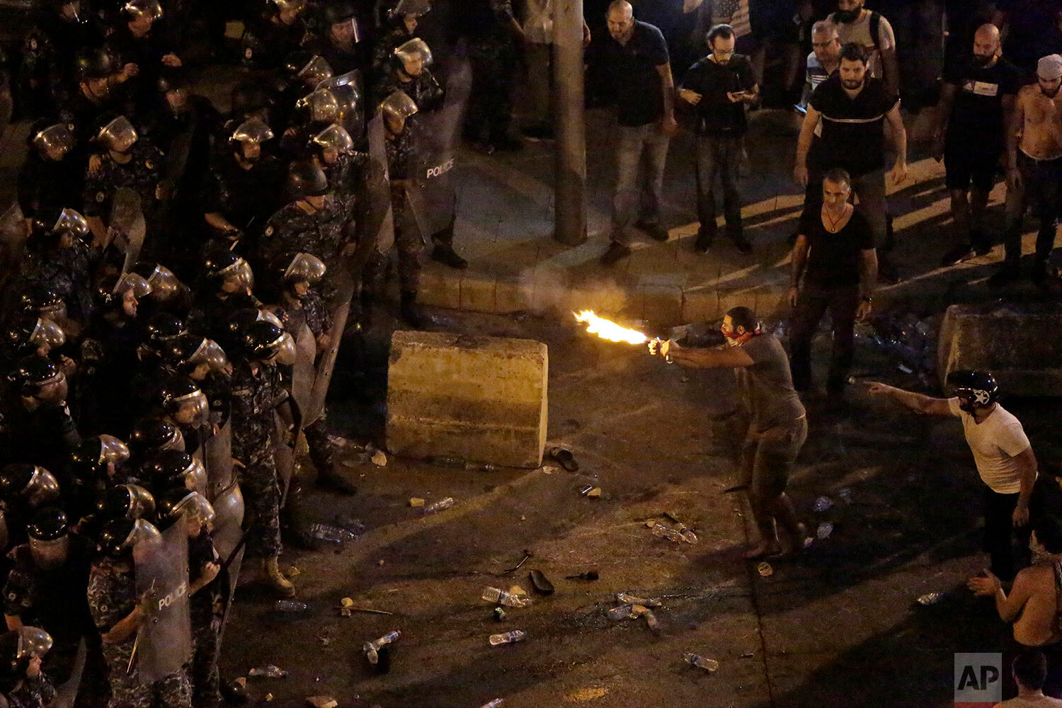Anti-government protesters clash with riot policemen during a protest against government's plans to impose new taxes in Beirut, Lebanon, Friday, Oct. 18, 2019. Lebanon erupted in protests Thursday over the government's plans to impose new taxes amid a severe economic crisis, taking their anger on politicians they accuse of widespread corruption and decades of mismanagement. (AP Photo/Hassan Ammar)