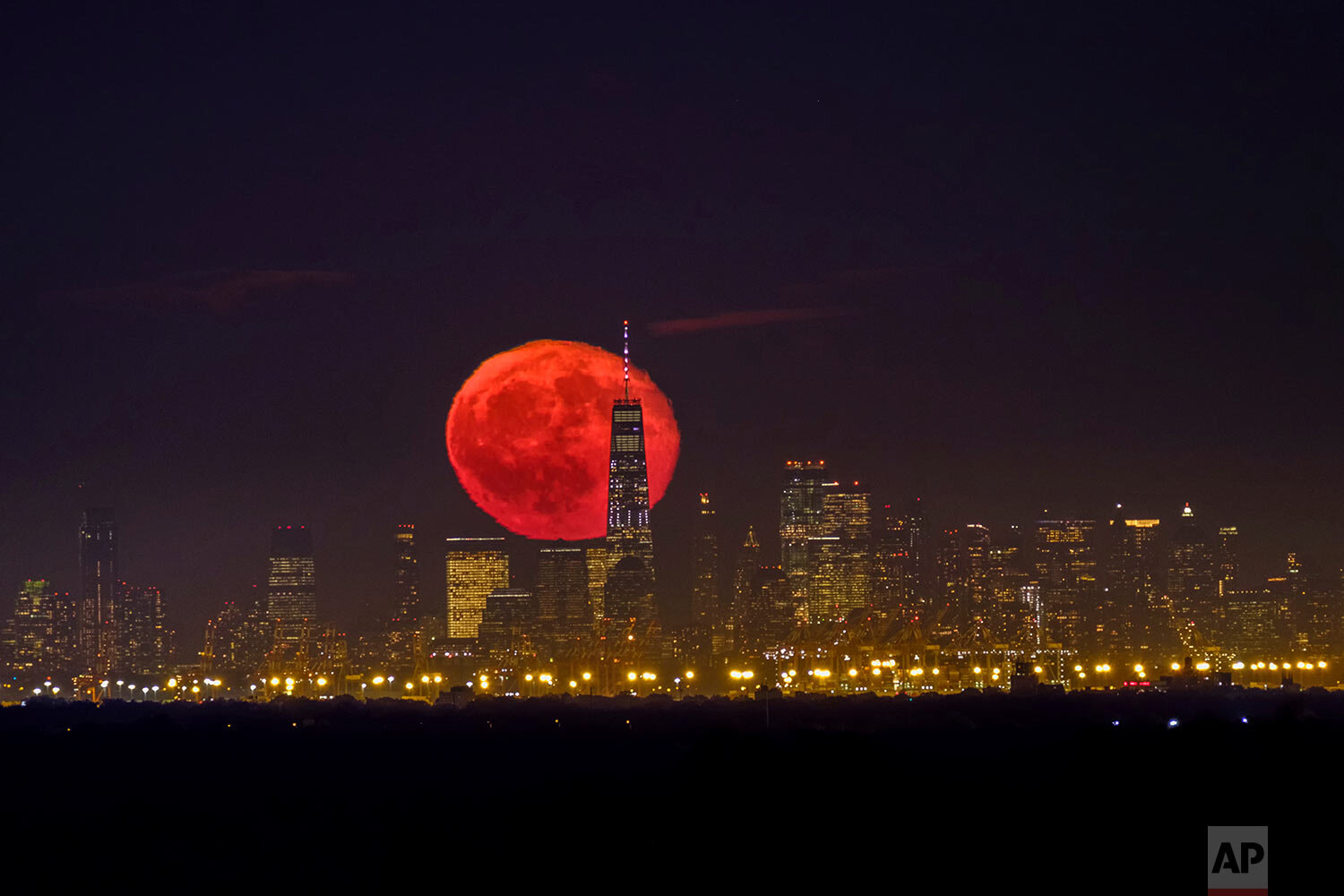 The moon rises behind One World Trade Center on a clear night in Lower Manhattan neighborhood of New York, as seen from Green Brook Township, N.J., Tuesday, Oct. 15, 2019. (AP Photo/J. David Ake)