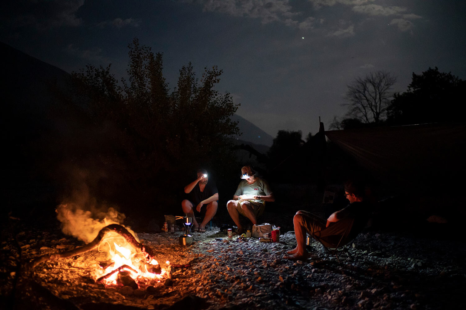 "Jurgen Steinbauer, Benedikt Baumler and Sebastian Baumler, German tourists who are kayaking the length of the Vjosa River, cook a meal as they sit next to a bonfire on the river bank in Albania. After seeing the Kalivac dam construction site, Benedikt Baeumler said, ""It was really unbelievable what they did to nature, removing entire parts of the mountain. I hope this dam is never built."" (AP Photo/Felipe Dana)"