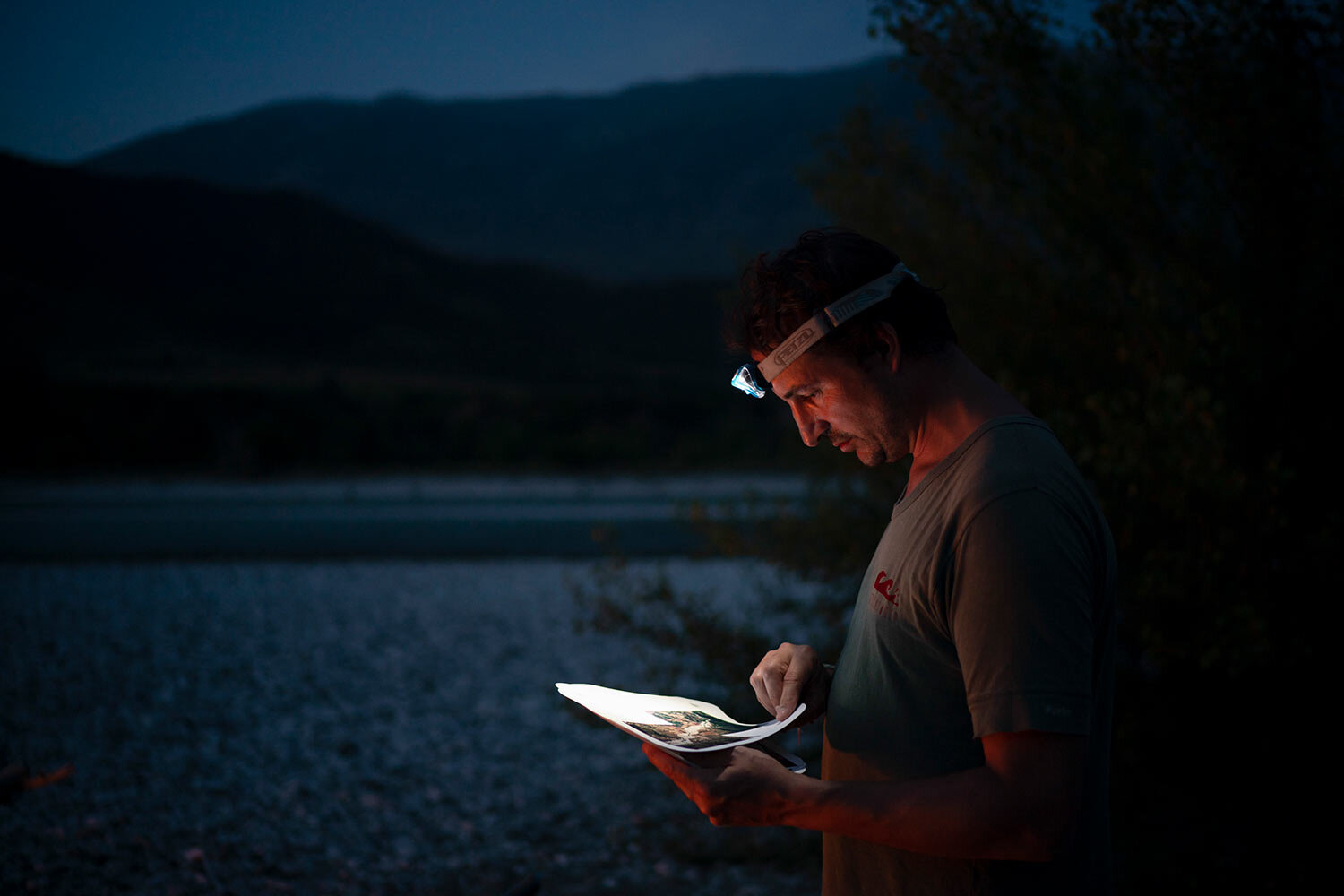 Benedikt Baeumler, a German advertising executive kayaking the length of the Vjosa River, checks his map after setting up camp on its bank in Albania. (AP Photo/Felipe Dana)