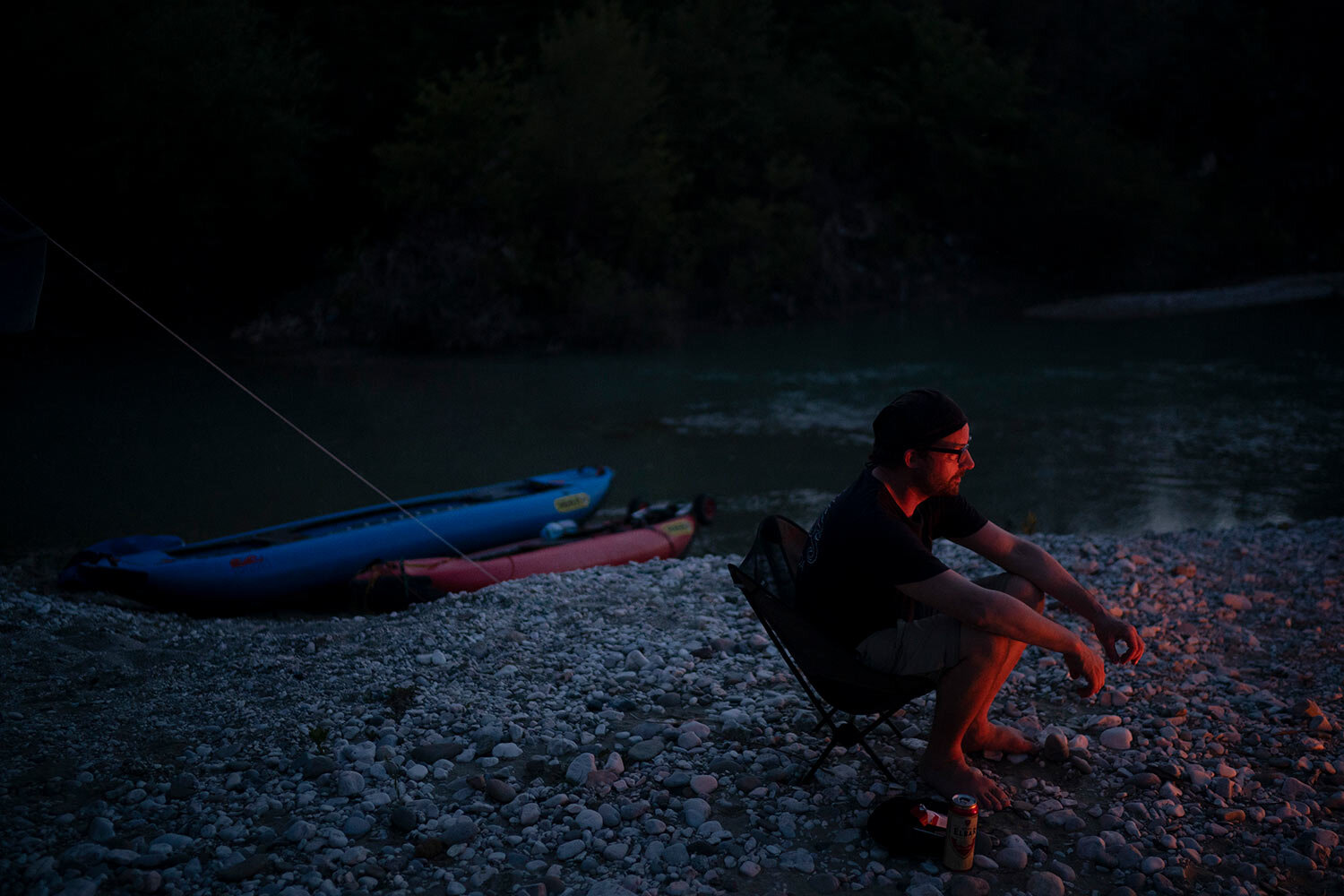 Sebastian Bäumler, 41, a German filmmaker kayaking the length of the Vjosa River, is illuminated by a bonfire as he sits next to his kayak on its bank in Albania. (AP Photo/Felipe Dana)