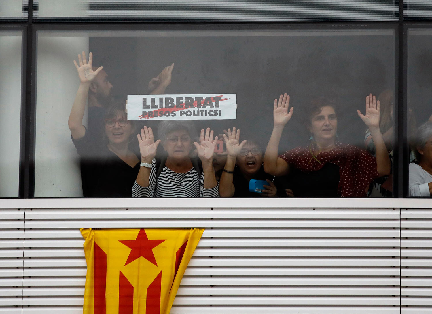 """Protesters stand behind a banner reading in Catalan, """"Freedom for Political Prisoners"""" at El Prat airport in Barcelona, Spain, Monday, Oct. 14, 2019. (AP Photo/Emilio Morenatti)"""