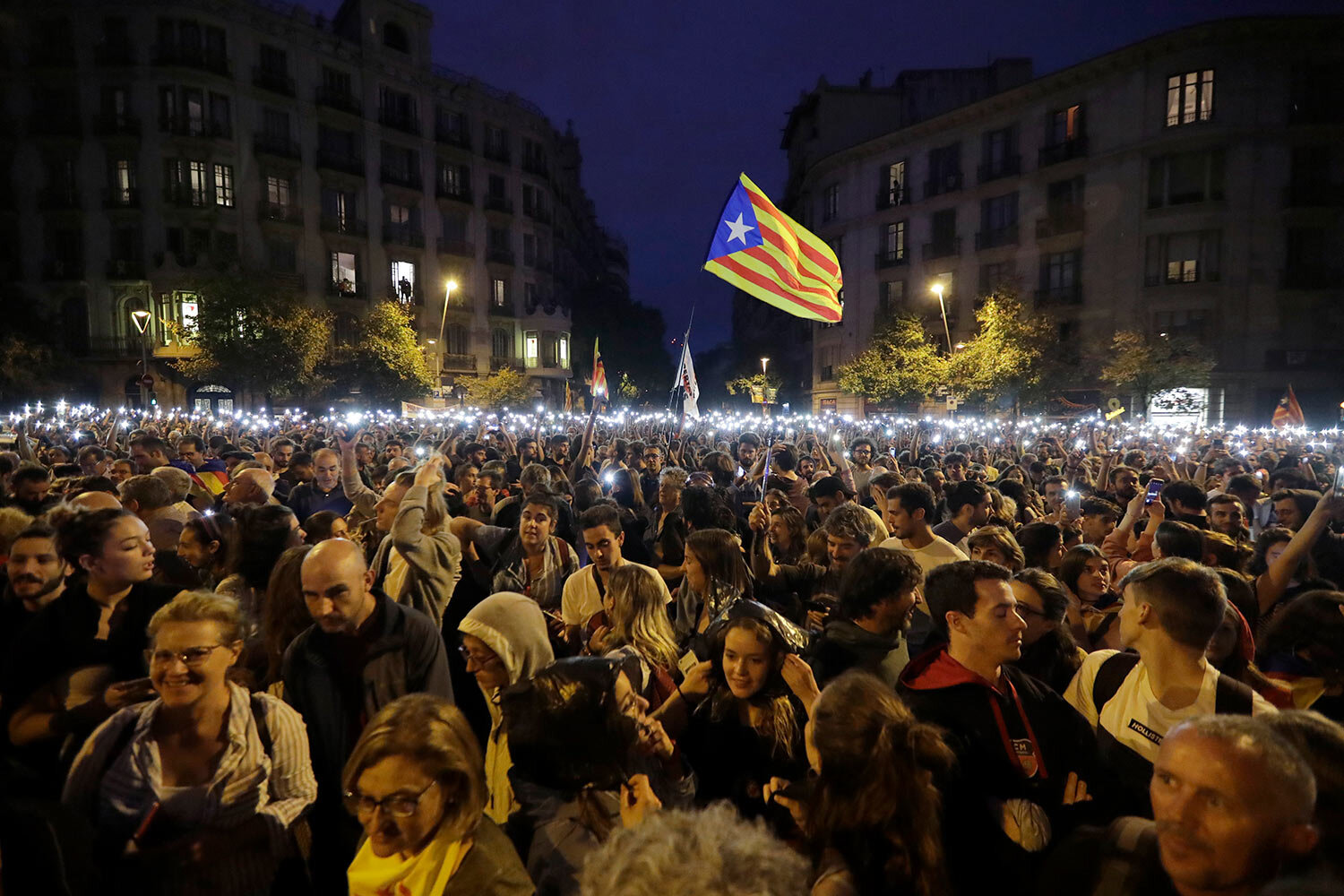 People hold up their phones with the torches switched on during a Catalan pro-independence protest in Barcelona, Spain, Sunday, Oct. 20, 2019. (AP Photo/Ben Curtis)