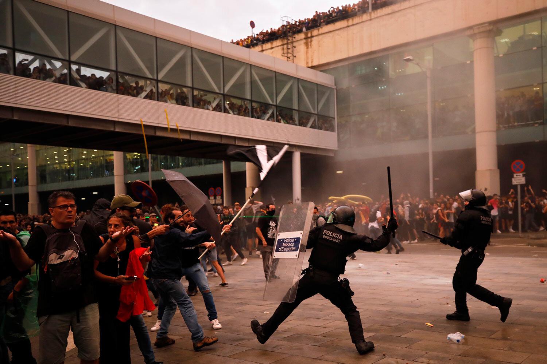 Riot policemen clash with protestors outside El Prat airport in Barcelona, Spain, Monday, Oct. 14, 2019.  (AP Photo/Emilio Morenatti)