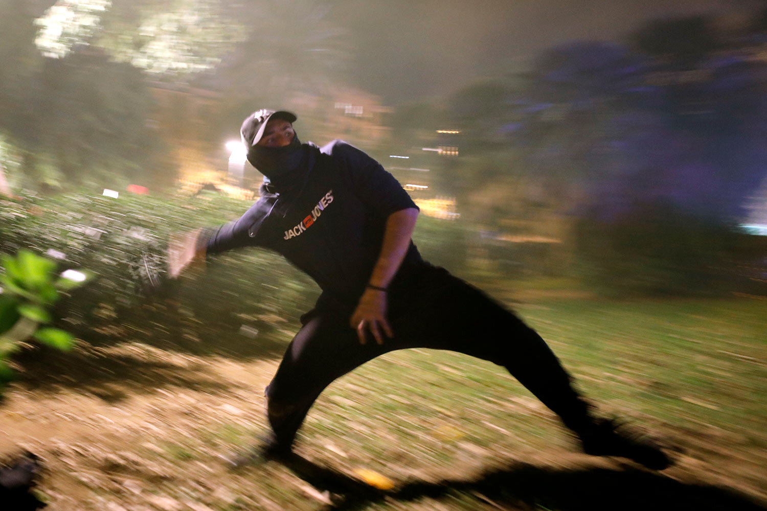 A protestor hurls a rock at police during clashes in Barcelona, Spain, Wednesday, Oct. 16, 2019. (AP Photo/Emilio Morenatti)