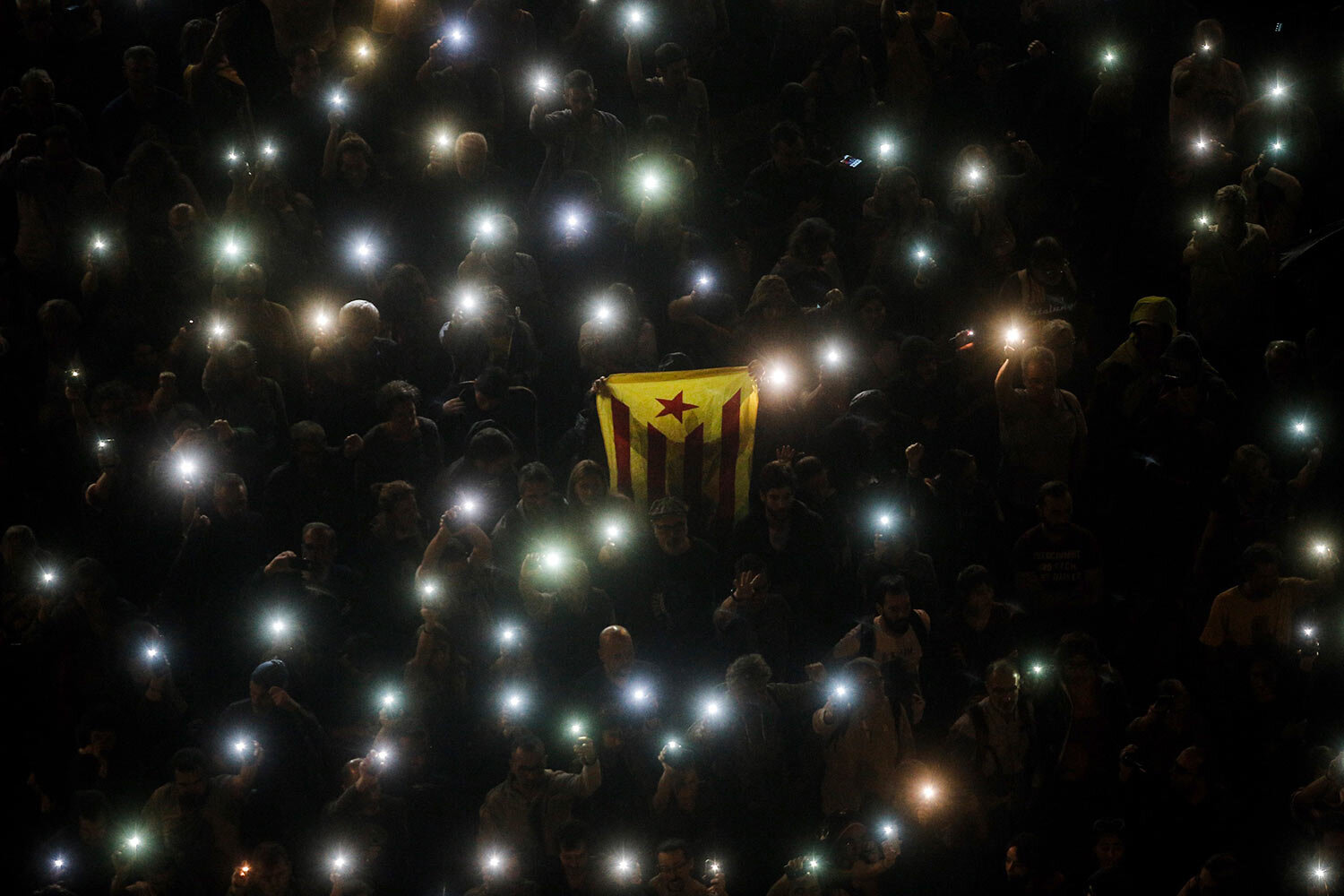 A Catalonian independence flag is held up as people hold up their phones with the torches switched on during a Catalan pro-independence protest in Barcelona, Spain, Sunday, Oct. 20, 2019. (AP Photo/Joan Mateu)