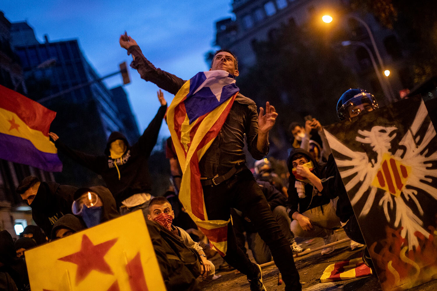 A Catalan pro-independence protestor throws a stone during clashes with police in Barcelona, Spain, Friday, Oct. 18, 2019.(AP Photo/Bernat Armangue)