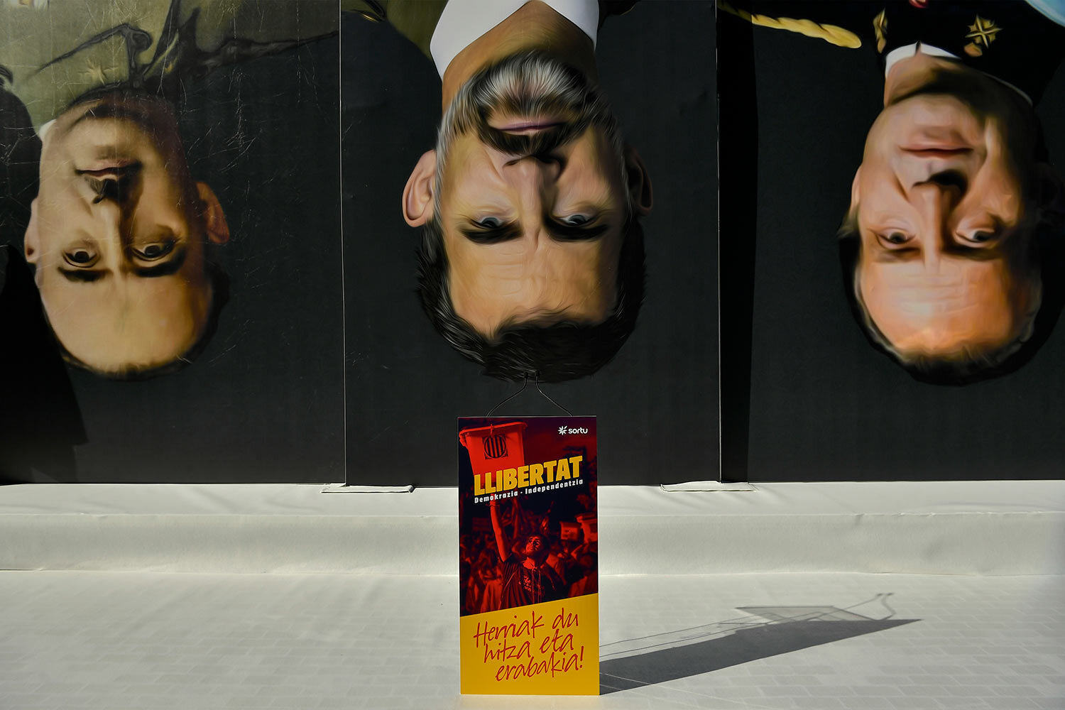Giant paintings of Spanish King Felipe VI, center, late Spanish dictator Francisco Franco, left, and former Spanish King Juan Carlos I, are face down behind a poster reading in Basque ''Freedom. (AP Photo/Alvaro Barrientos)