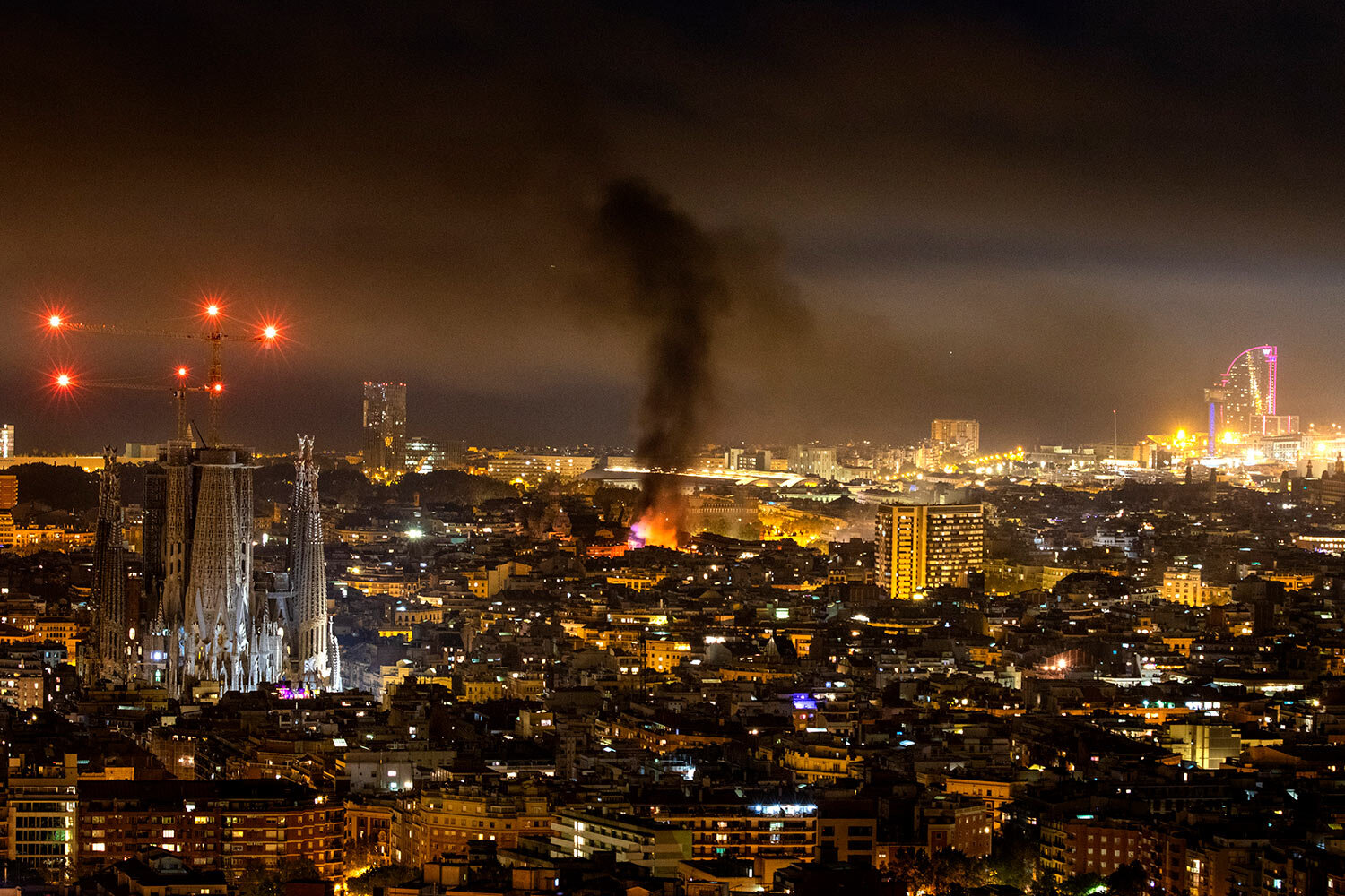 In this Friday, Oct. 18, 2019 photo, smoke caused by fires set by pro-independence demonstrators rises over Barcelona, Spain. (AP Photo/Joan Monfort)