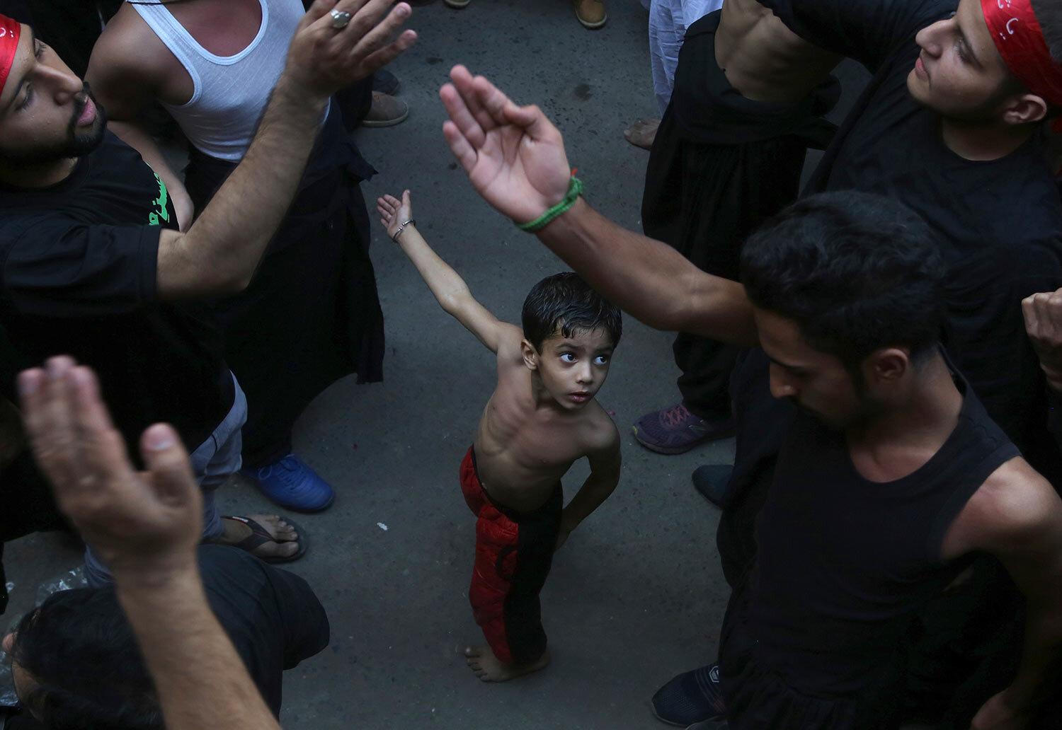 A Shiite Muslim child beats his chest next to his father during a procession to mark the end of the 40-day mourning period following the anniversary of the 7th century death of Imam Hussein, the Prophet Muhammad's grandson and one of Shiite Islam's most beloved saints, in Lahore, Pakistan, Sunday, Oct. 20, 2019. (AP Photo/K.M. Chaudary)
