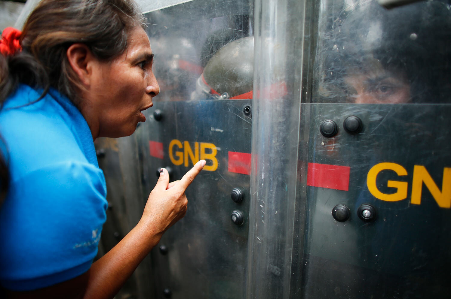 An opposition protester talks to soldiers of the National Guard blocking the way to the headquarters of the state electricity company in Caracas, Venezuela, Thursday, Oct. 24, 2019. Demonstrators mobilized in support of the inhabitants of the western state of Zulia, who suffer daily power outages that sometimes last more than 20 hours. (AP Photo/Ariana Cubillos)
