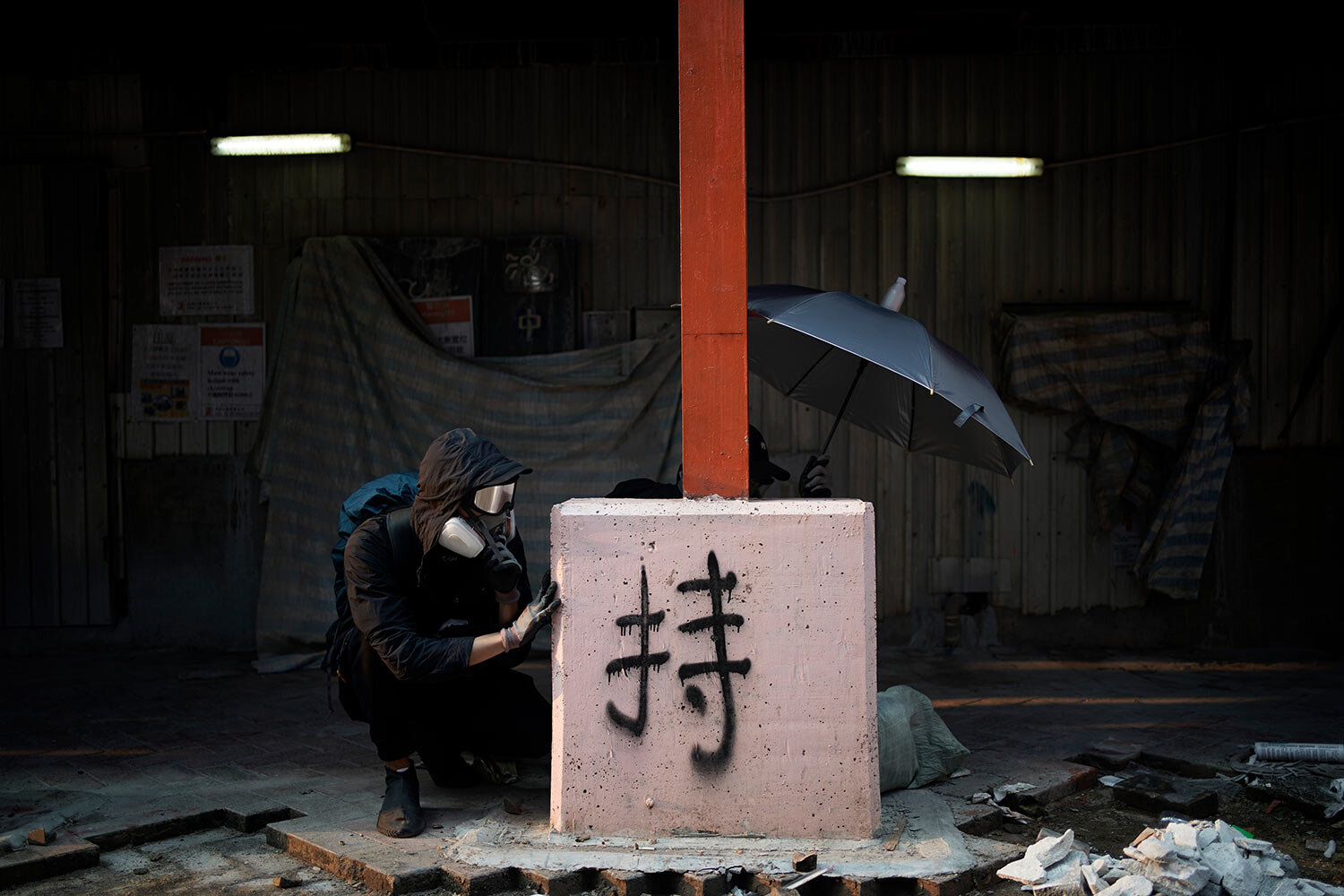 Protesters take cover during a confrontation with police in Hong Kong, Sunday, Oct. 20, 2019, ignoring a ban on the rally and setting up barricades amid tear gas and firebombs. Demonstrations since June have called for full democracy and police accountability. (AP Photo/Felipe Dana)