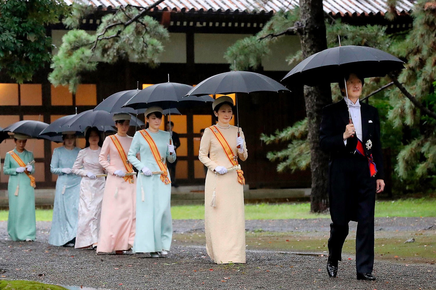 """Japan's Crown Prince Akishino, right, and Crown Princess Kiko, second from right, arrive for the ceremony at """"Kashikodokoro"""", one of three shrines at the Imperial Palace, in Tokyo, Tuesday, Oct. 22, 2019. Emperor Naruhito and Empress Masako visited three Shinto shrines at the Imperial Palace before Naruhito proclaimed himself Japan's 126th emperor in an enthronement ceremony. (Kyodo News via AP)"""