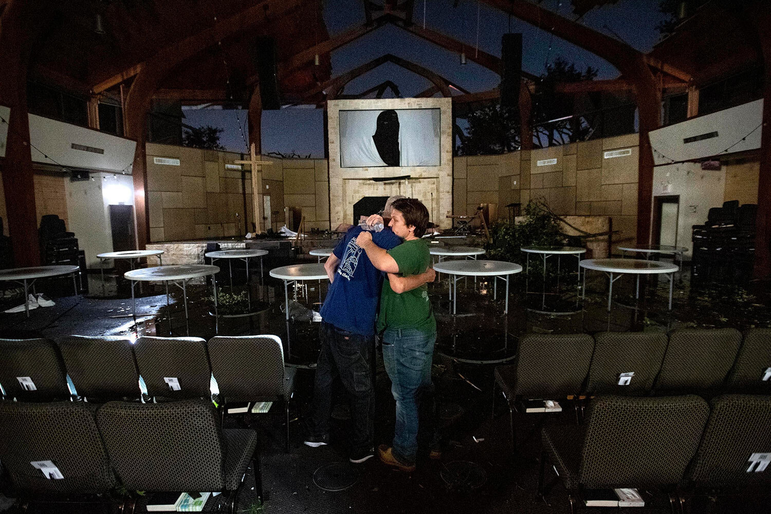 Matt Younger, right, a pastor at Northway Church, embraces facilities associate Robert Lusk in their church's severely damaged sanctuary on Sunday, Oct. 20, 2019, after a tornado tore through North Dallas. (AP Photo/Jeffrey McWhorter)