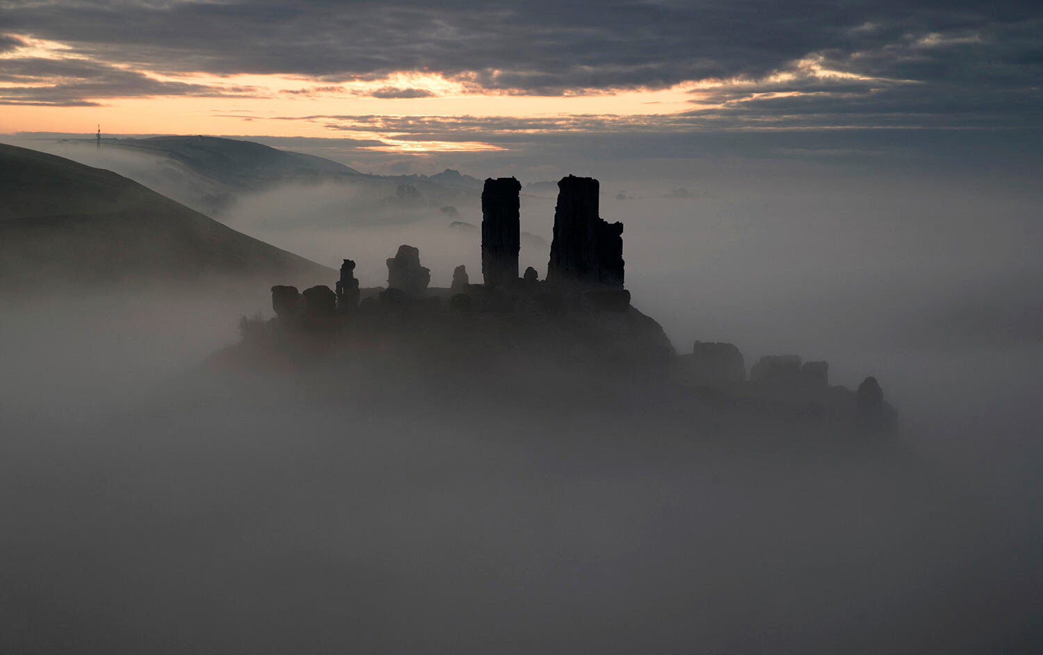 The sun begins to rise behind a mist covered Corfe Castle in Dorset, England, Tuesday, Oct. 22, 2019. (Andrew Matthews/PA via AP)