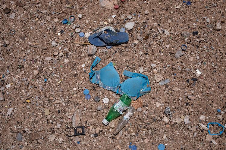 """حمالة صدر على الأرض حيث يُحتجز المهاجرون الأفارقة في مجمعات صحراوية تُعرف بالعربية باسم """"حوش"""" في شبوة ، اليمن.  (AP Photo / ناريمان المفتي)"""
