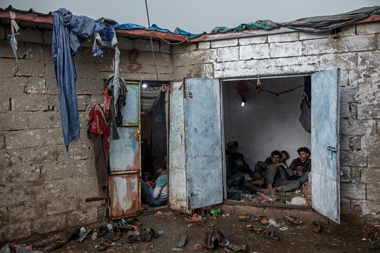 Yemenis, right, chew qat, while Ethiopian migrants, left, take shelter in a small shack at a qat market in Dhale province in Yemen. (AP Photo/Nariman El-Mofty)