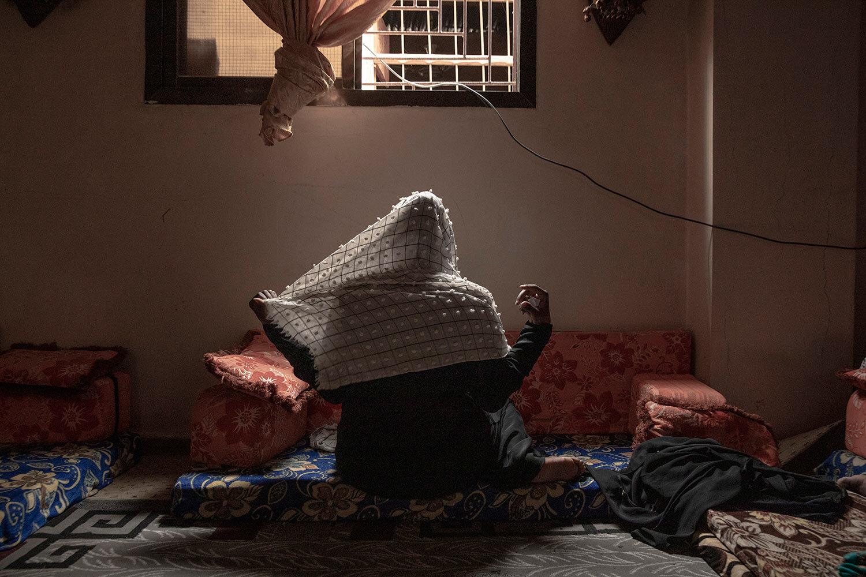 المهاجرة الإثيوبية زهرة ، وهي ضحية للاغتصاب ، تضبط حجابها لالتقاط صورة لها في البساتين ، وهي منطقة عدن ، اليمن.  (AP Photo / ناريمان المفتي)