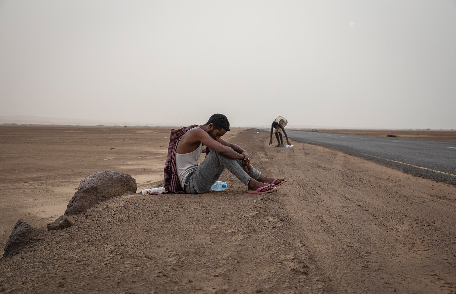 Ethiopian migrants rest on the side of a highway in Lahj, Yemen, early in the morning, as they make their way to Aden. (AP Photo/Nariman El-Mofty)