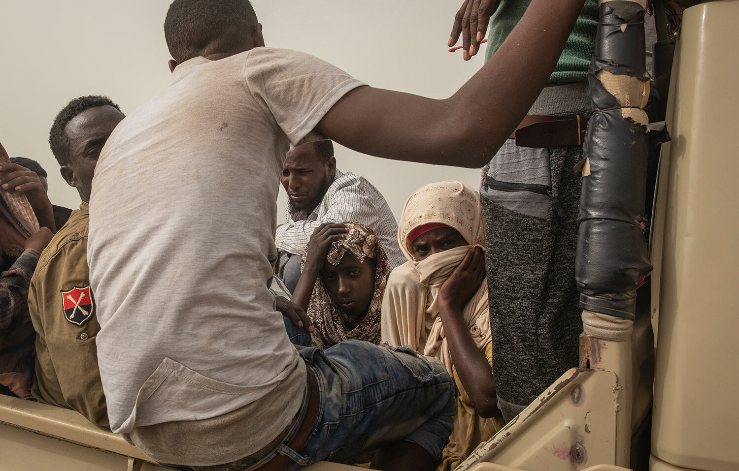 "Ethiopian migrants sit in the back of a pickup truck to be taken to desert compounds known in Arabic as ""hosh,"" in Ras al-Ara, Lahj, Yemen. (AP Photo/Nariman El-Mofty)"