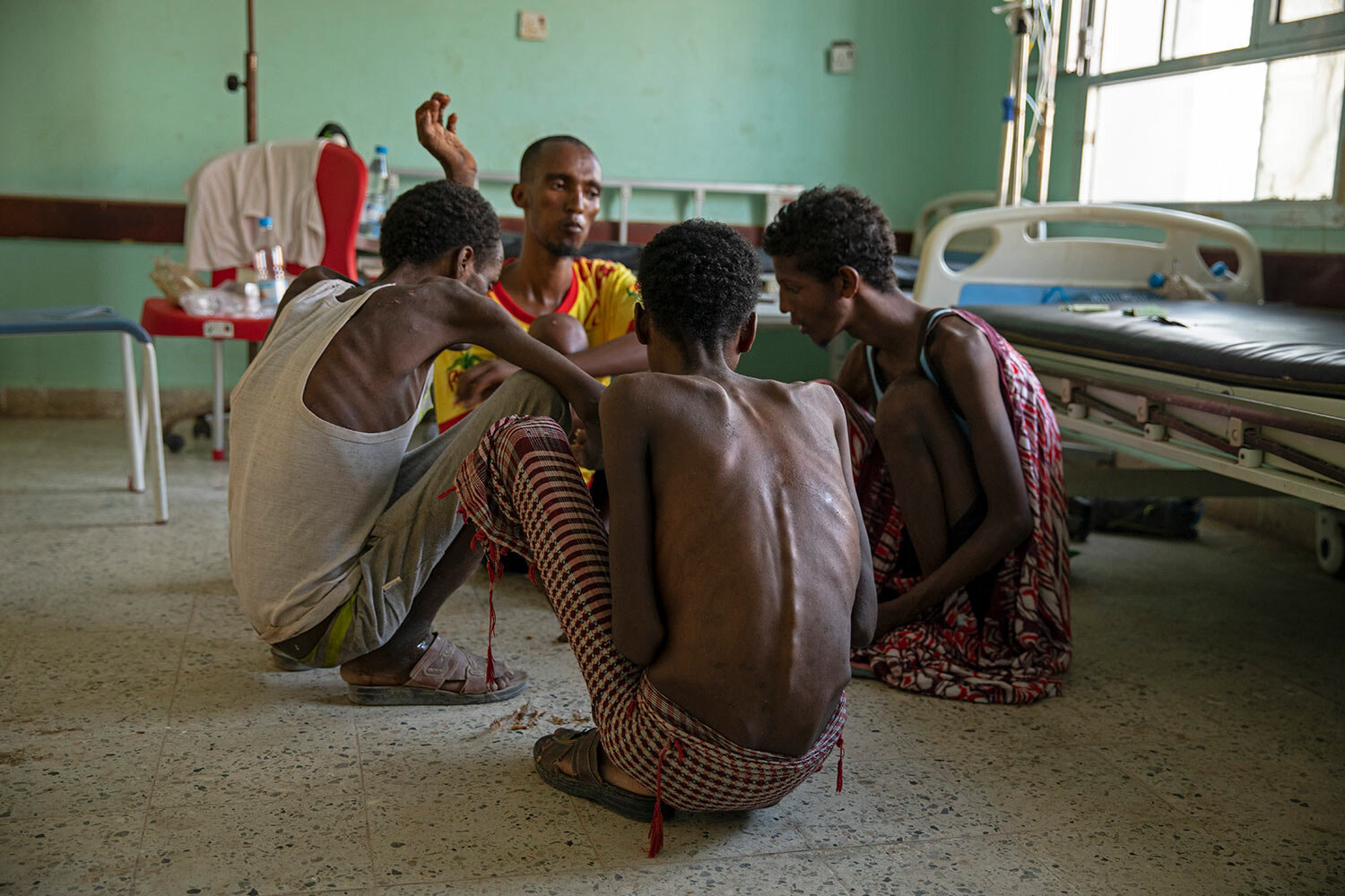 Ethiopian migrants, from center background to right, Gamal Hassan, Abdu Yassin, Mohammed Hussein, and Abdu Mohammed, who were imprisoned by traffickers for months, eat rice from a bowl on the floor, at the Ras al-Ara Hospital in Lahj, Yemen. They said they were fed once a day with scraps of bread and a sip of water when they were held. (AP Photo/Nariman El-Mofty)