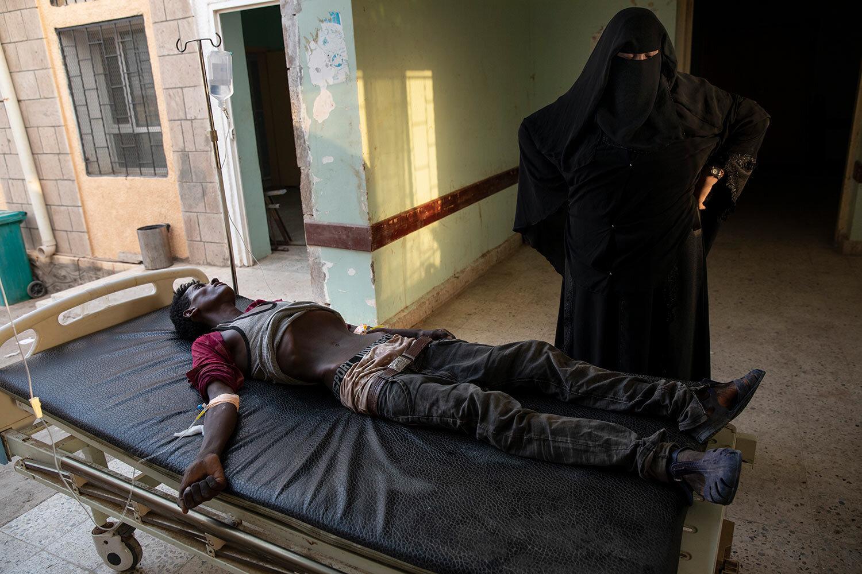 مهاجر تيغري إثيوبي سُجن على يد مهربين لعدة أشهر ، يرقد على مصحوبة بممرضة في مستشفى رأس العرا في لحج ، اليمن.  أعطته الممرضات السوائل لكنه توفي بعد عدة ساعات.  (AP Photo / ناريمان المفتي)