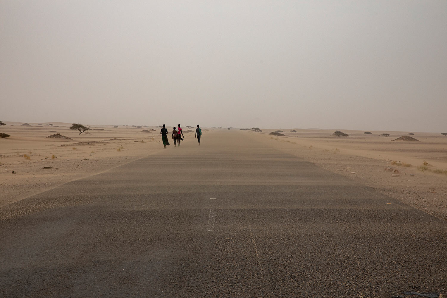 Ethiopian migrants walk along a road in a sandstorm in Lahj, Yemen. (AP Photo/Nariman El-Mofty)