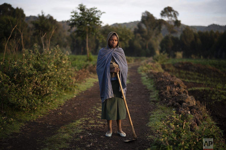 13-year-old farmer Julienne poses for a photo in Kinigi, Rwanda. (AP Photo/Felipe Dana)