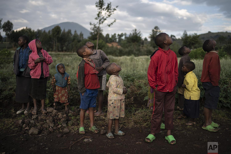 Children watch a drone flying near the Volcanoes National Park in Kinigi, Rwanda. (AP Photo/Felipe Dana)