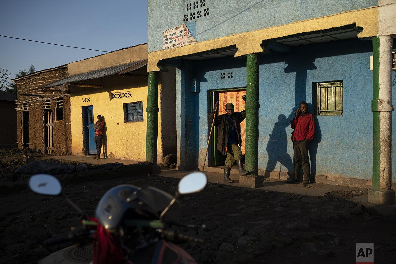 Residents stand outside as the sun rises in Kinigi, Rwanda. (AP Photo/Felipe Dana)