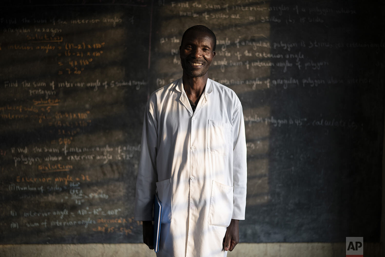 Fabien Uwimana, a French and English teacher, poses for a photo at the Nyabitsinde Primary School in Kinigi, Rwanda. (AP Photo/Felipe Dana)