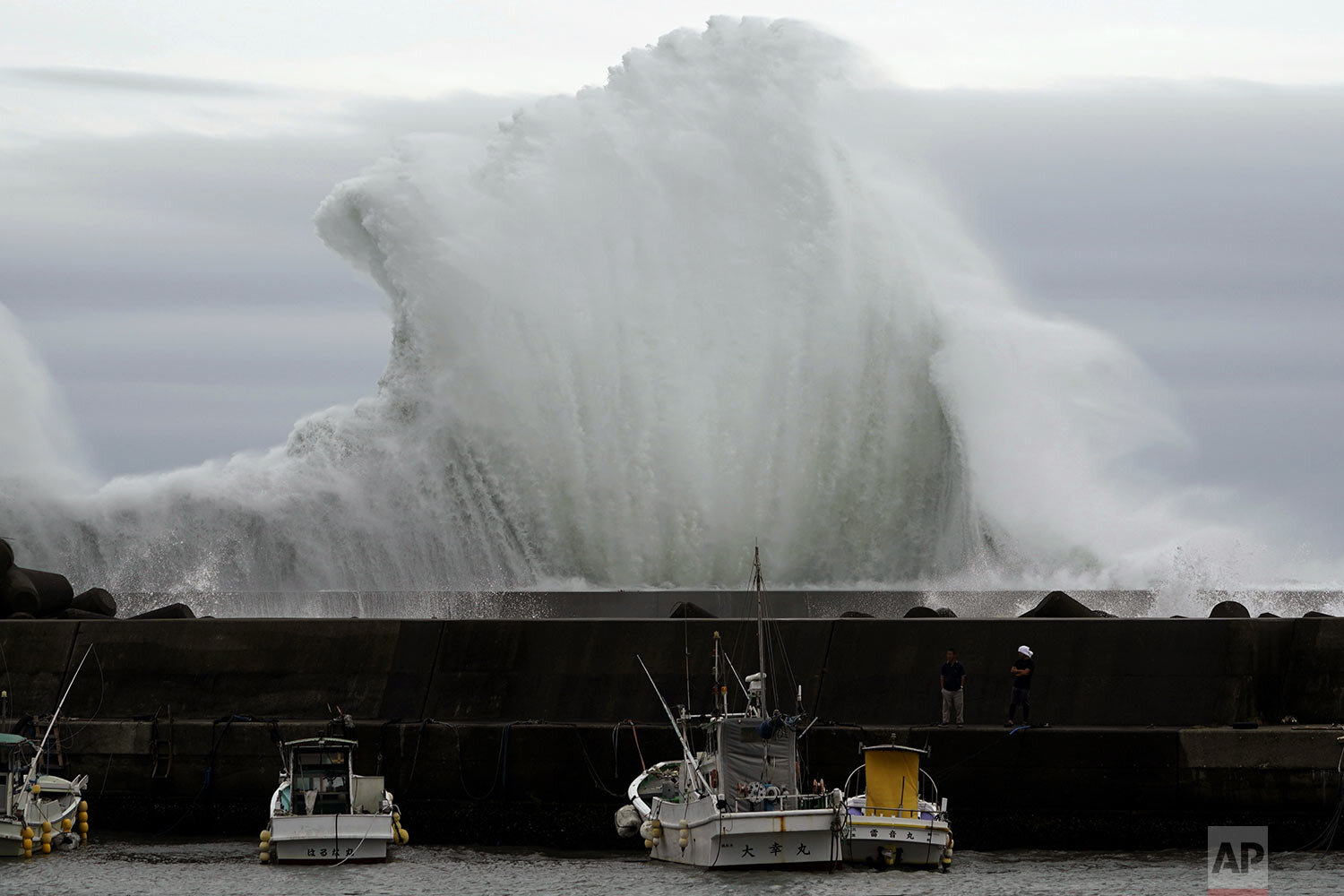 Men look at fishing boats as surging waves hit against the breakwater while Typhoon Hagibis approaches at a port in town of Kiho, Mie Prefecture, Japan Friday, Oct. 11, 2019.  (AP Photo/Toru Hanai)